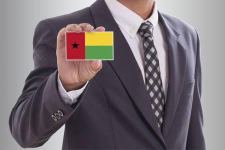 guinea bissau: Businessman holding a business card with Guinea Bissau Flag  Stock Photo