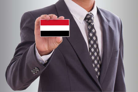 lag: Businessman in suit holding a business card with Yemen Flag