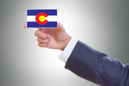 patiotic: Businessman hand holding a business card with Colorado Flag