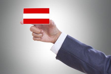 Businessman hand holding a business card with Austria Flag  photo