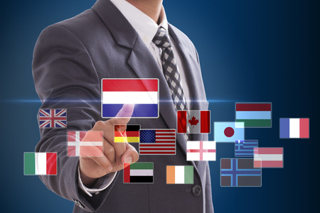 Businessman pushing on a touch screen interface, choosing Dutch Flag