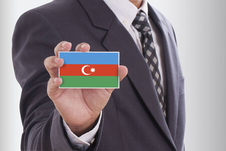 Businessman in suit holding a business card with Azerbaijan Flag  photo