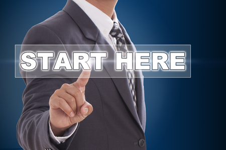 Businessman hand touching start here on screen  photo