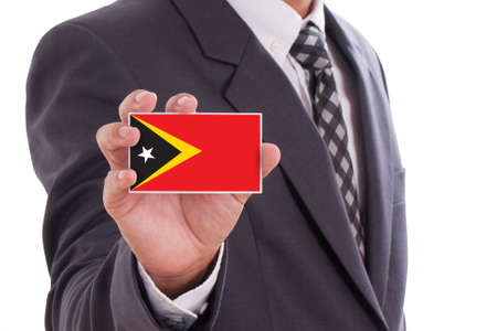 timor: Businessman holding a business card with East Timor Flag  Stock Photo