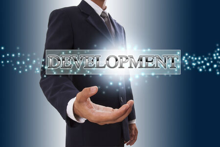 Businessman hand showing development button on virtual screens  photo