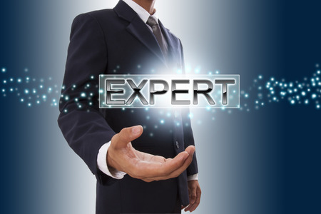 perito: Empresario mano que muestra el bot�n de expertos en la pantalla virtual Foto de archivo