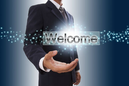 Businessman hand showing welcome button on virtual screen   photo