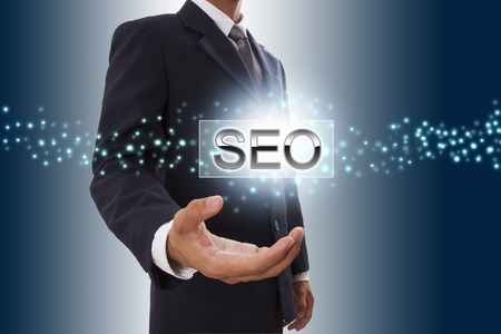 Businessman hand showing SEO button on virtual screen   photo