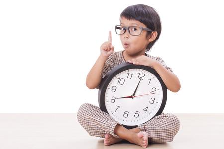 El muchacho lindo está sosteniendo un reloj grande aislado en el fondo blanco Foto de archivo