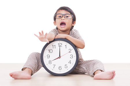 early morning: Cute boy is holding big clock isolated on white background