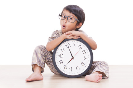 Cute boy is holding big clock isolated on white background  photo