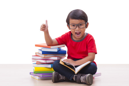 Cute boy reading a book and showing thumb up sign
