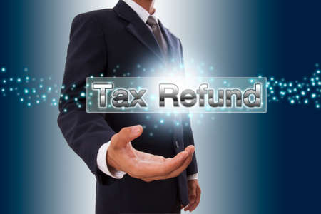 refund: Businessman hand showing tax refund button on virtual screen.