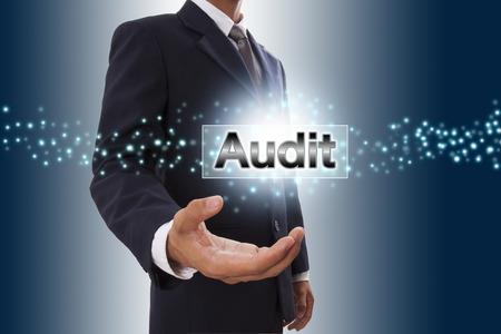 El hombre de negocios mano que muestra el botón de auditoría en la pantalla virtual.