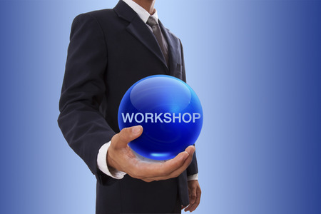 Businessman hand holding blue crystal ball with workshop word. photo