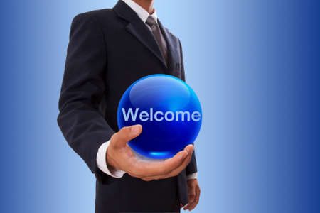 Businessman hand holding blue crystal ball with welcome word. photo