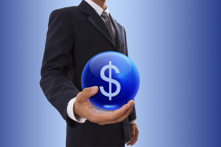 Businessman hand holding blue crystal ball with dollar sign icon. photo