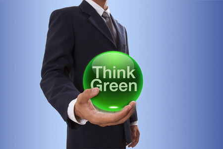Businessman hand holding blue crystal ball with think green word. photo