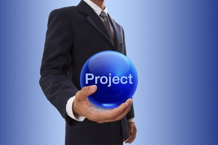 implement: Businessman hand holding blue crystal ball with project word.