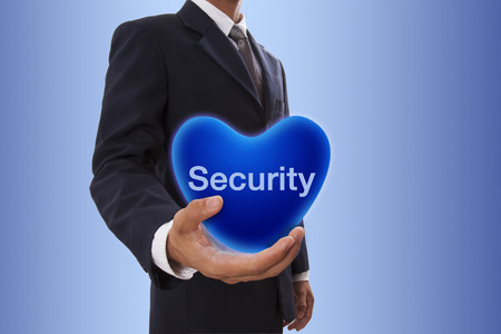 Businessman hand holding blue heart bubble with security word photo