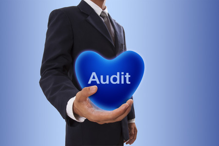 Businessman hand holding blue heart bubble with audit word photo