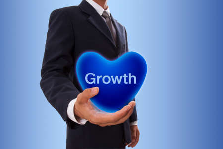 Businessman hand holding blue heart bubble with growth word photo