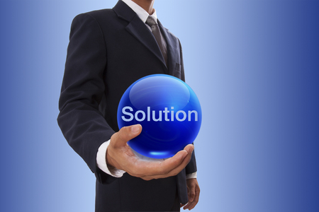 Businessman hand holding blue crystal ball with solution word. photo
