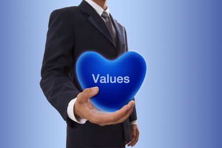 Businessman hand holding blue heart bubble with values word