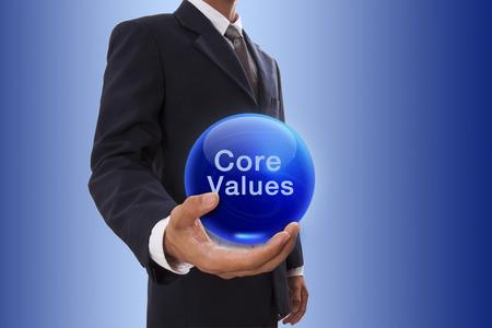 コア値単語で青い水晶玉を持っているビジネスマン手。