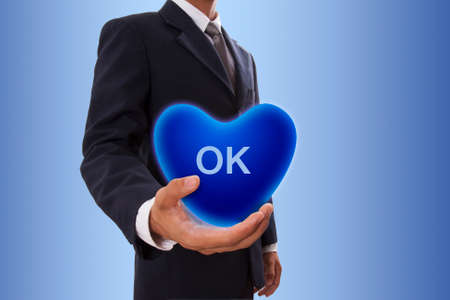 winning proposal: Businessman hand holding blue heart bubble with ok sign