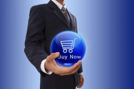 Businessman hand holding blue crystal ball with buy now icon. photo