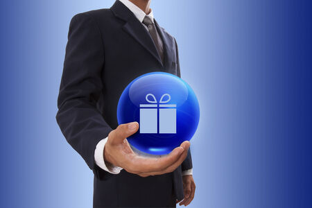 Businessman hand holding blue crystal ball with gift symbol. photo