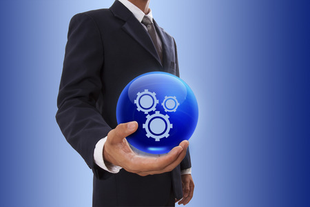 Businessman hand holding blue crystal ball with gears symbol. photo