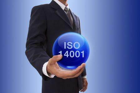 Businessman hand holding blue crystal ball with iso 14001 word.