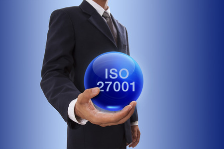Businessman hand holding blue crystal ball with iso 27001 word. photo