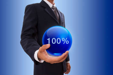 Businessman hand holding blue crystal ball with 100 percent. photo