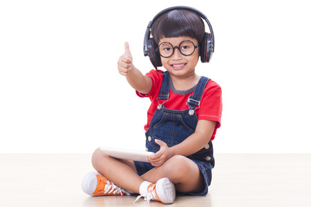 Happy boy with headphones connected to a tablet to listen to music and showing thumb up photo