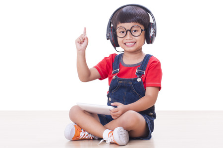 Happy boy with headphones connected to a tablet to listen to music and pointing up photo
