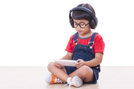Happy boy with headphones connected to a tablet to listen to music Happy boy with headphones connected to a tablet to listen to music photo