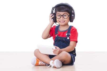 Happy boy with headphones connected to a tablet to listen to music photo