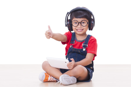 Happy boy with headphones connected to a tablet to listen to music