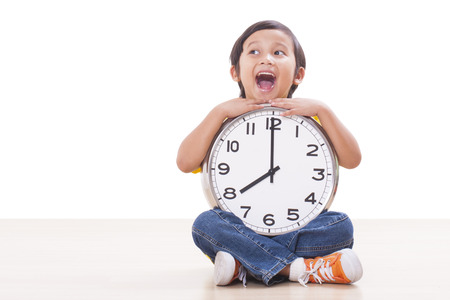 Boy is holding big clock showing eight a.m