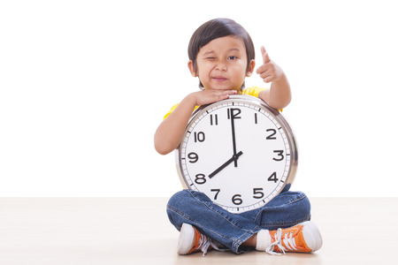 Boy is holding big clock showing eight a.m photo