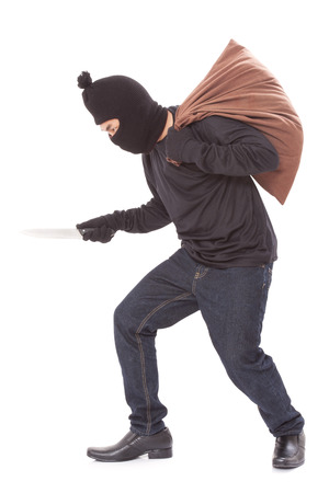 Thief with bag and holding knife, isolated on white background photo