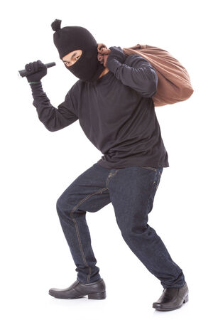 Thief with bag and holding flashlight, isolated on white background photo