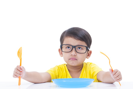 Little boy waiting for food with spoon and fork at table