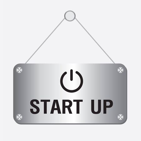 silver metallic start up sign hanging on the wall