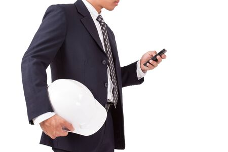 indenture: engineer holding white helmet with using smartphone isolated on white background Stock Photo