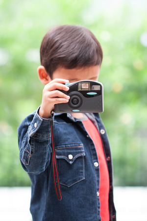 compact camera: Cute boy using compact camera. Stock Photo