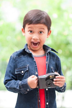 compact camera: Happy asian boy using a compact camera